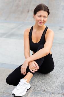 Vista frontal de uma bela mulher em athleisure posando ao ar livre