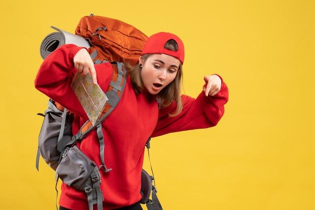 Vista frontal de uma bela viajante feminina com uma mochila segurando um mapa apontando para o chão