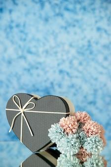 Vista frontal de uma caixa com flores coloridas em forma de coração preto em azul desfocado
