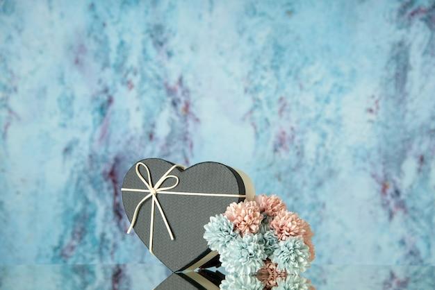 Vista frontal de uma caixa de flores pretas em forma de coração refletida no espelho com um azul