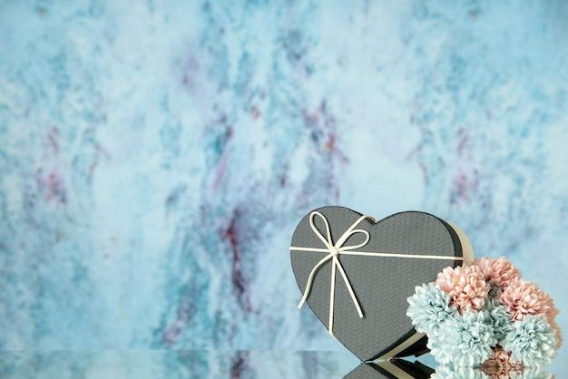 Vista frontal de uma caixa em forma de coração preto com flores coloridas em azul