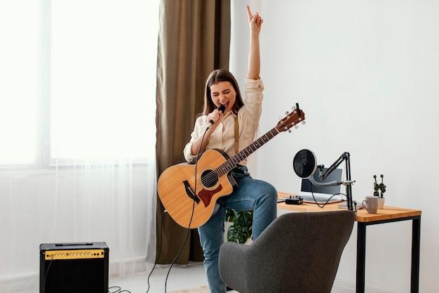 Vista frontal de uma cantora cantando e gravando música com violão