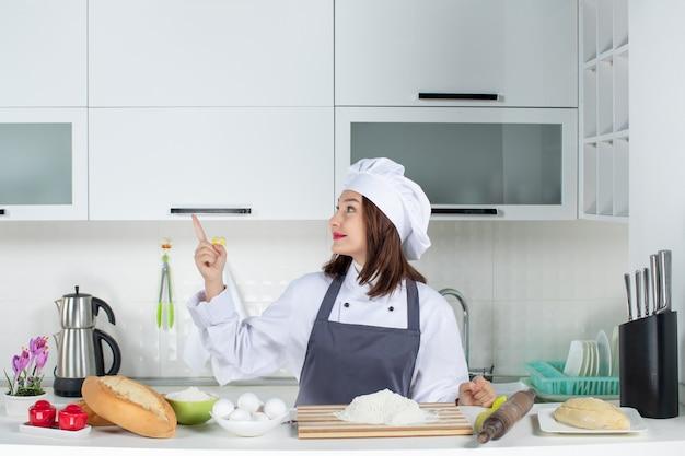 Vista frontal de uma chef feminina confiante de uniforme em pé atrás da mesa com legumes e verduras de pão apontando para cima na cozinha branca