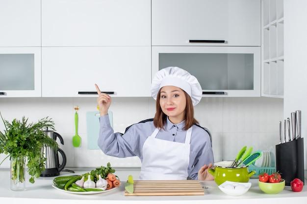 Vista frontal de uma chef sorridente e de legumes frescos apontando para cima no lado direito da cozinha branca