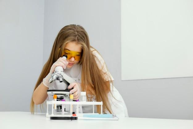 Vista frontal de uma cientista com óculos de segurança e microscópio