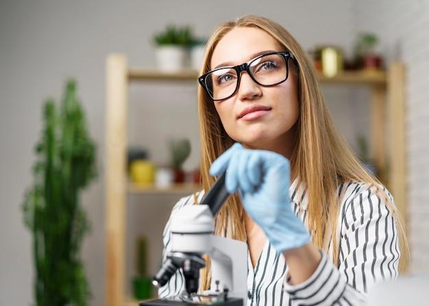 Vista frontal de uma cientista com um microscópio sonhando acordado