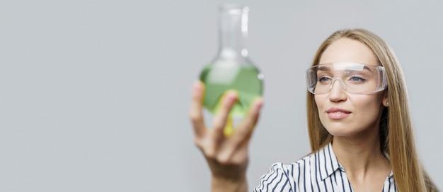 Vista frontal de uma cientista segurando um tubo de ensaio com espaço de cópia