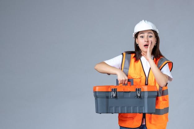 Vista frontal de uma construtora carregando uma caixa de ferramentas pesada na parede branca