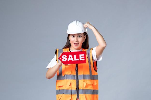 Vista frontal de uma construtora segurando uma placa vermelha de venda na parede branca