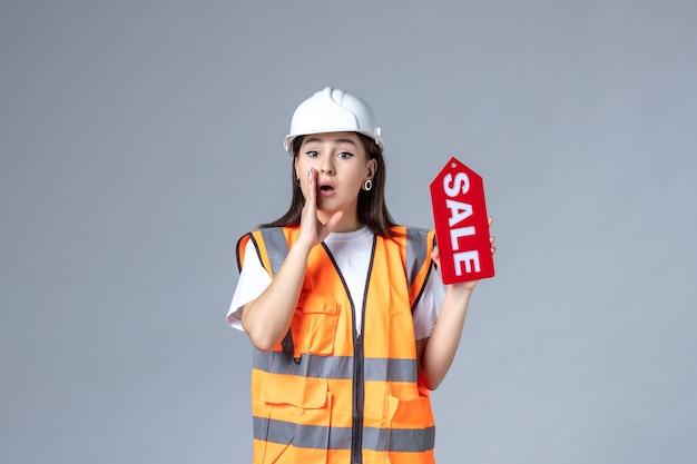 Vista frontal de uma construtora segurando uma placa vermelha de venda na parede cinza