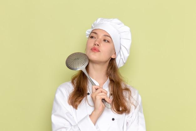 Vista frontal de uma cozinheira de terno branco, segurando uma colher de prata grande e pensando na parede verde