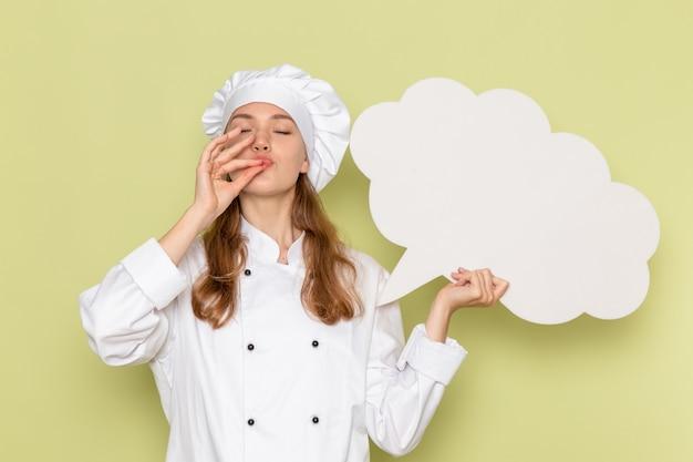 Vista frontal de uma cozinheira de terno branco segurando uma enorme placa branca na parede verde