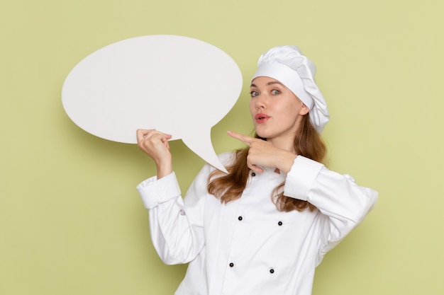 Vista frontal de uma cozinheira de terno branco segurando uma placa branca na parede verde
