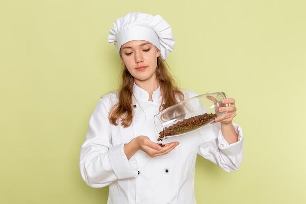 Vista frontal de uma cozinheira em um terno de cozinheira branco segurando uma lata com sementes de café na parede verde