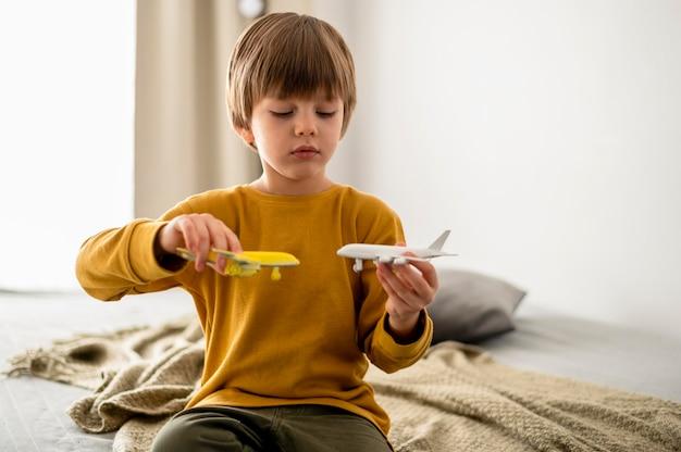 Vista frontal de uma criança brincando com bonecos de avião
