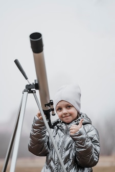 Vista frontal de uma criança usando um telescópio