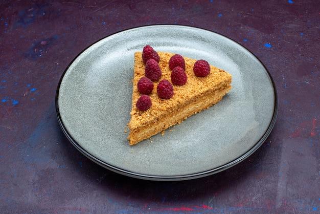 Vista frontal de uma deliciosa fatia de bolo com framboesas na superfície escura