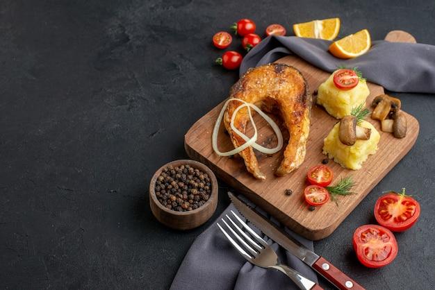 Vista frontal de uma deliciosa refeição de peixe frito com cogumelos, tomate, queijo na placa de madeira, rodelas de limão, pimenta na toalha de cor escura talheres na superfície preta