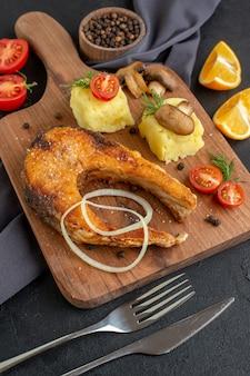 Vista frontal de uma deliciosa refeição de peixe frito com cogumelos, vegetais, queijo, tábua de madeira, fatias de limão, pimenta em toalha de cor escura talheres em superfície preta angustiada