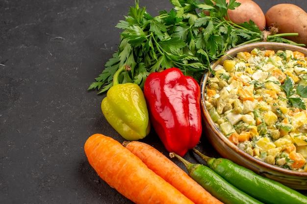 Vista frontal de uma deliciosa salada com legumes frescos em superfície escura
