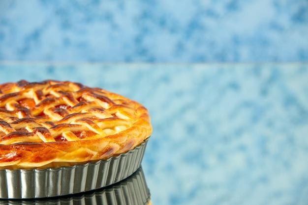 Vista frontal de uma deliciosa torta de frutas dentro da fôrma de bolo em uma mesa azul clara
