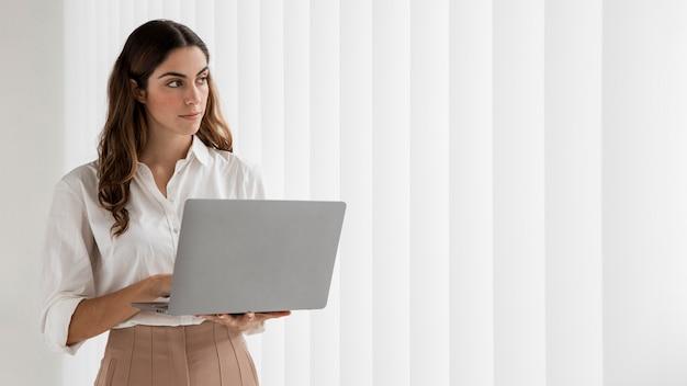 Vista frontal de uma elegante empresária usando laptop com espaço de cópia