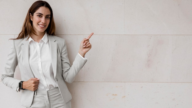 Vista frontal de uma elegante mulher de negócios apontando para a direita