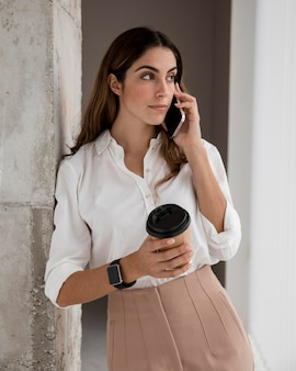 Vista frontal de uma empresária falando ao telefone enquanto toma um café