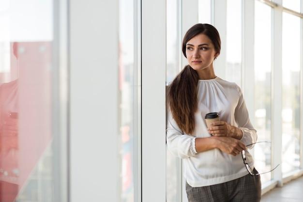 Vista frontal de uma empresária posando com uma xícara de café
