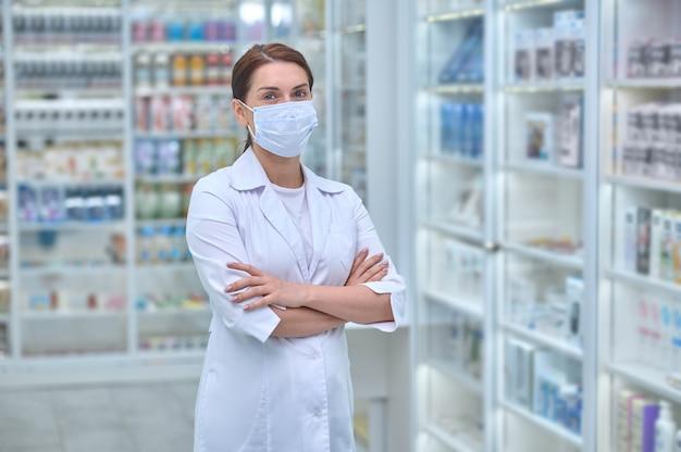 Vista frontal de uma farmacêutica com os braços cruzados em pé entre as prateleiras com produtos de saúde