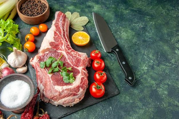 Vista frontal de uma fatia de carne fresca com tomates em um açougueiro azul-escuro para alimentos carne cozinha animal frango cor vaca açougueiro