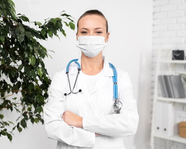 Vista frontal de uma fisioterapeuta com máscara médica