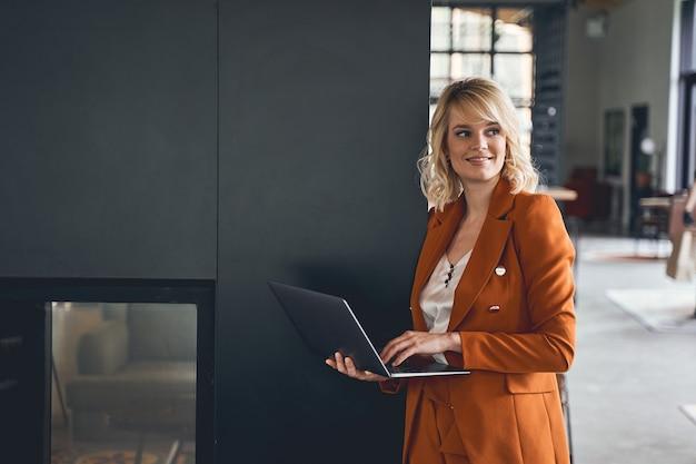 Vista frontal de uma freelancer feminina relaxada e sorridente com um laptop na mão, olhando para longe