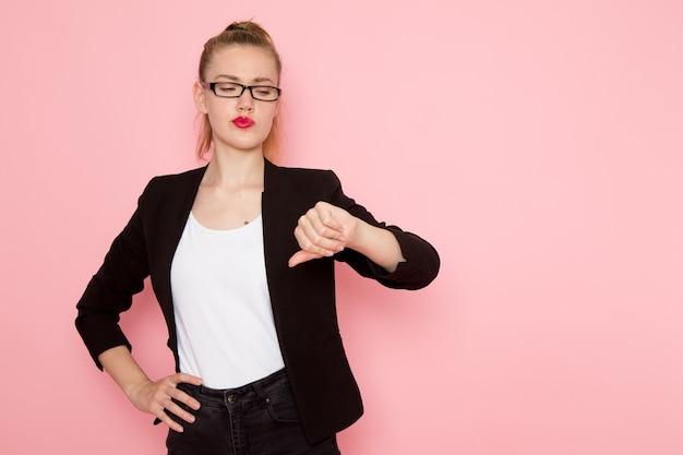 Vista frontal de uma funcionária de escritório com uma jaqueta preta, mostrando uma placa diferente na parede rosa claro