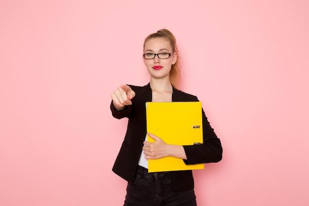 Vista frontal de uma funcionária de escritório com uma jaqueta preta segurando documentos na parede rosa claro