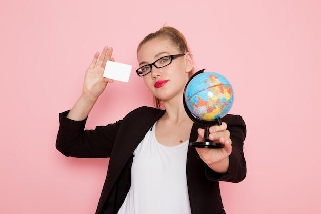Vista frontal de uma funcionária de escritório com uma jaqueta preta segurando o globo e um cartão na parede rosa claro