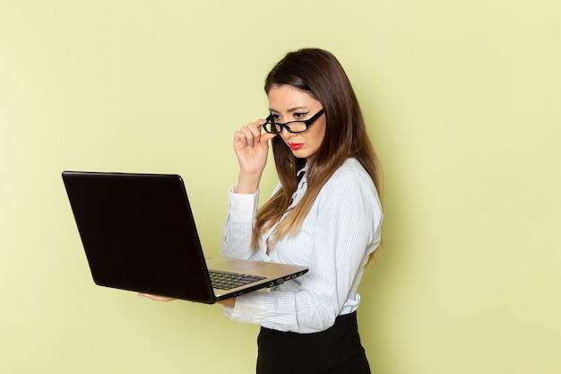 Vista frontal de uma funcionária de escritório de camisa branca e saia preta segurando o laptop na parede verde-clara