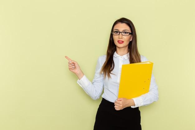 Vista frontal de uma funcionária de escritório de camisa branca e saia preta segurando uma pasta amarela na parede verde