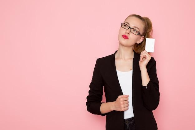 Vista frontal de uma funcionária de escritório em jaqueta preta, pensando, segurando um cartão branco na parede rosa
