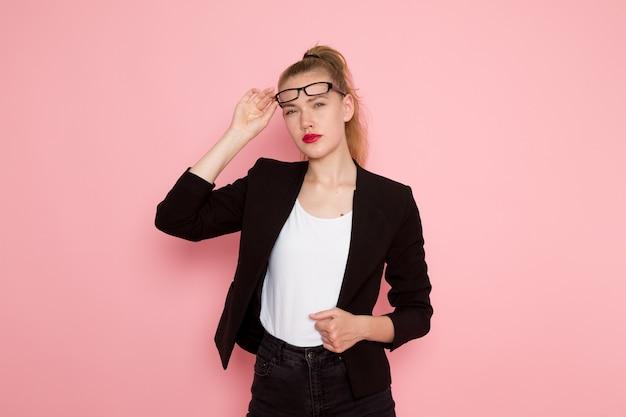 Vista frontal de uma funcionária de escritório em uma jaqueta preta e tirando os óculos de sol na parede rosa