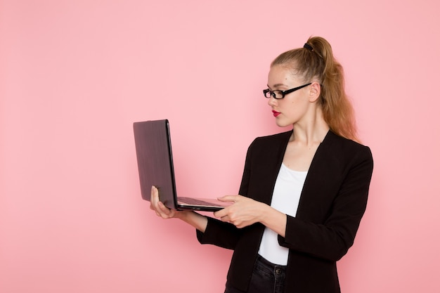Vista frontal de uma funcionária de escritório em uma jaqueta preta usando seu laptop na parede rosa