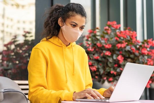 Vista frontal de uma garota com máscara facial na rua