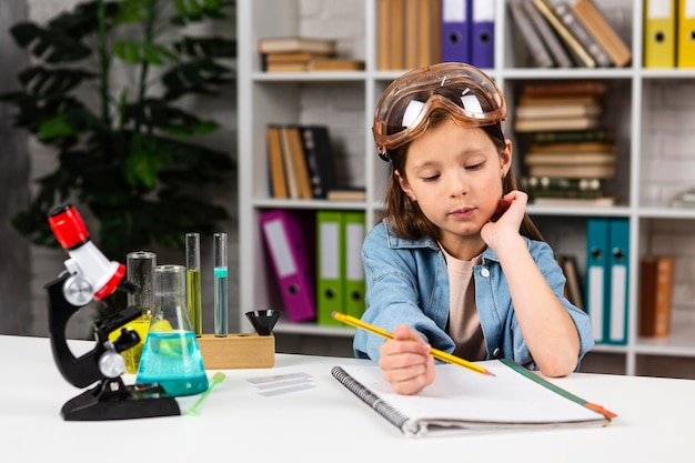 Vista frontal de uma garota com óculos de segurança fazendo experimentos científicos com microscópio