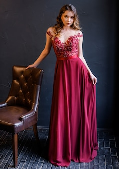 Vista frontal de uma garota elegante em um vestido vermelho se inclina em uma cadeira e olha para a câmera