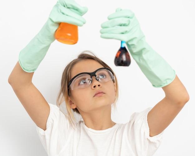 Vista frontal de uma garota fazendo experiências de química com tubos de ensaio