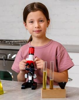Vista frontal de uma garota fazendo experimentos com microscópio