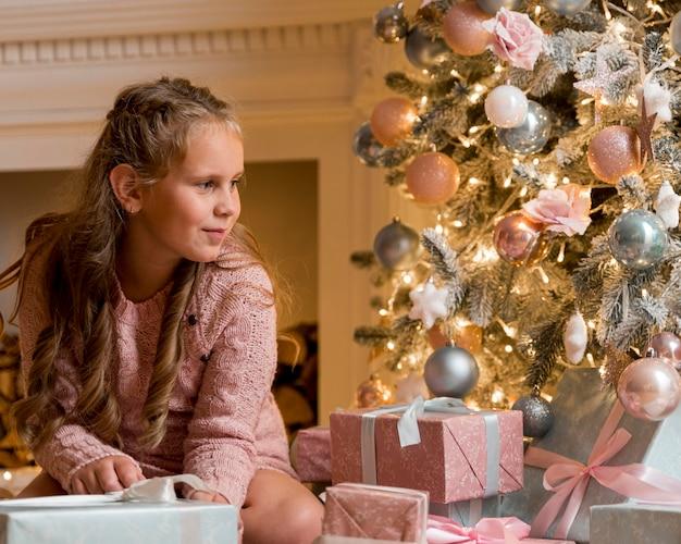 Vista frontal de uma garota feliz com presentes e árvore de natal