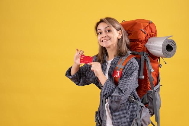 Vista frontal de uma garota loira com uma mochila vermelha segurando um cartão
