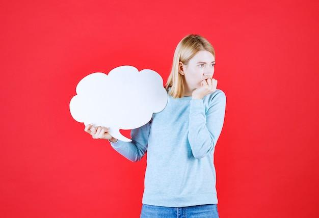 Vista frontal de uma garota pensativa segurando um cartaz e pensando em algo