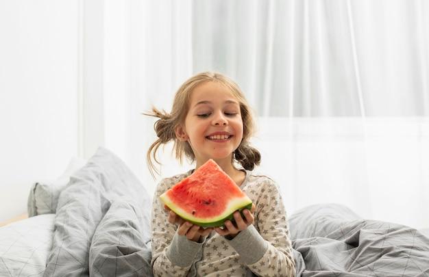 Vista frontal de uma garota sorridente na cama